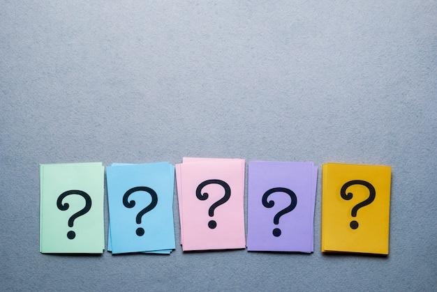 Fila de tarjetas de diferentes colores con signos de interrogación
