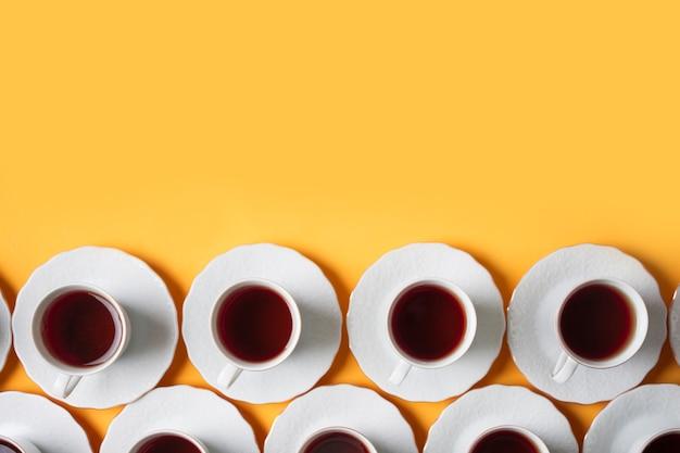 Fila de la taza de té blanco herbario en fondo amarillo