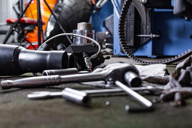 Fila de tornillos y herramientas de llave inglesa en un piso en el taller cerca de la bicicleta vieja reparada o motor de motocicleta. escena industrial con equipamiento