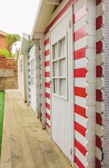 Fila de tres coloridas cabañas de rayas de playa en el jardín de una casa