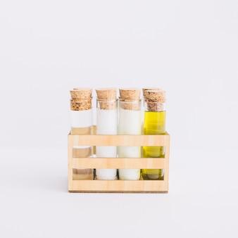 Fila de tubos de ensayo con productos de spa en recipiente de madera sobre fondo blanco