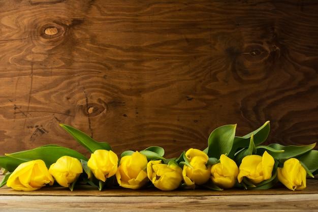 Fila de tulipanes amarillos sobre superficie de madera, espacio de copia