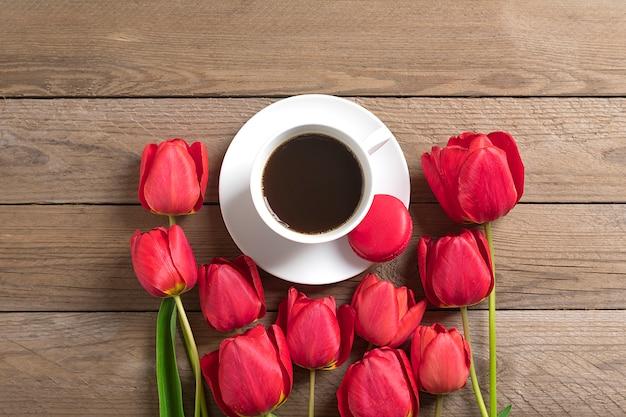 Fila de tulipanes rojos y taza de café negro americano sobre fondo de madera endecha plana
