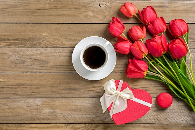 Fila de tulipanes rojos, taza de café negro americano