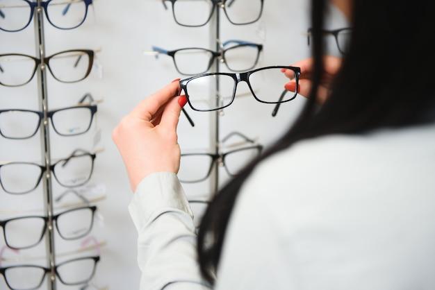 Fila de vasos en ópticas. tienda de anteojos. párese con gafas en la tienda de óptica. la mano de la mujer elige las gafas. corrección de la vista.