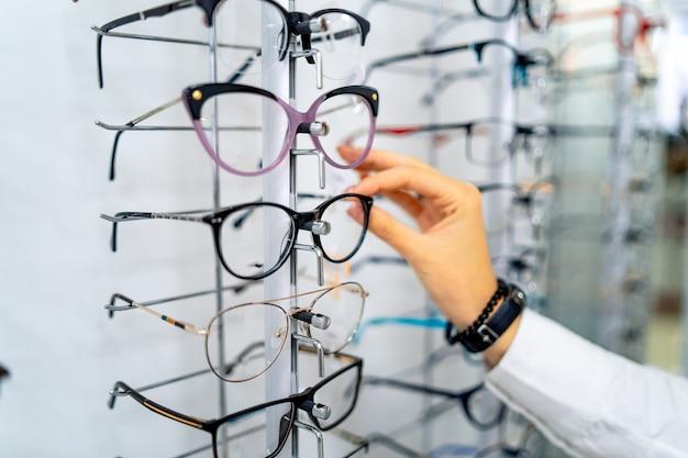 Fila de vasos en ópticas. tienda de anteojos. párese con gafas en la tienda de óptica.