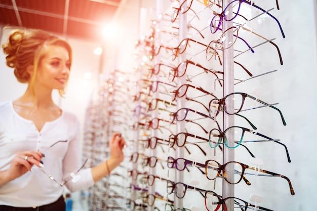 Fila de vasos en ópticas. tienda de anteojos. de pie con gafas en la tienda de óptica.