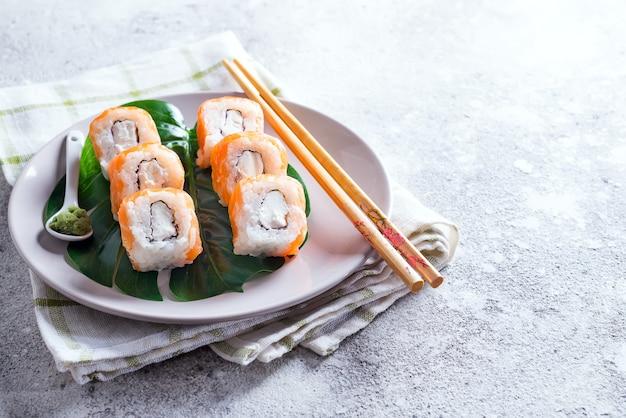 Filadelfia roll clásico en un plato con palillos. comida japonesa de sushi.