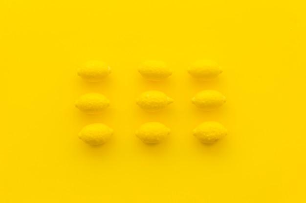 Filas de caramelos de limón sobre fondo amarillo