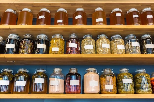 Filas de conservas en frascos de vidrio en estantes arbolados