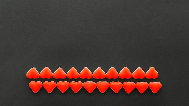 Filas de caramelos de forma de corazón rojo sobre fondo negro