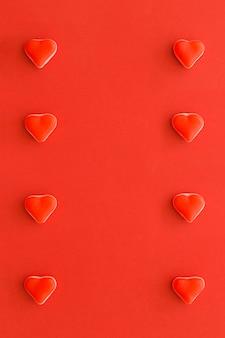 Filas de caramelos de forma de corazón sobre fondo rojo