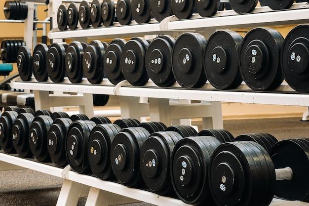 Filas de mancuernas en el gimnasio con alto contraste y tono de color monocromático