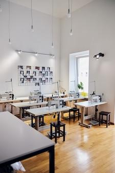 Filas de mesas con máquinas de coser e imágenes en la pared blanca en el taller