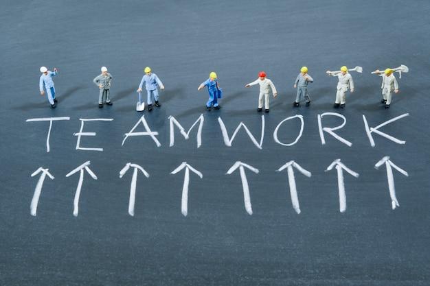 Filas de personas trabajadoras en miniatura y la palabra trabajo en equipo en la pizarra