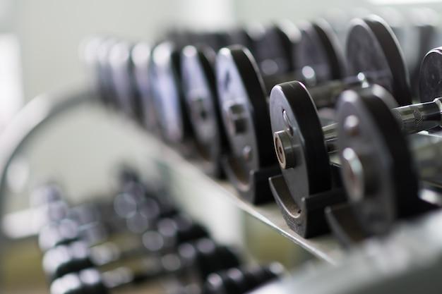 Filas de pesas de metal en rack en el gimnasio / club deportivo. equipo del entrenamiento del peso.