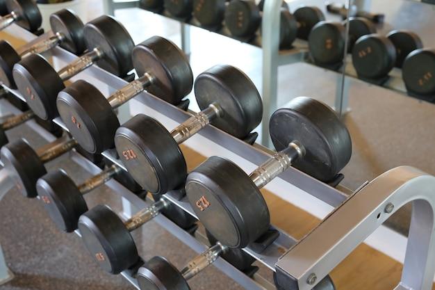 Filas de pesas de metal en rack en el gimnasio