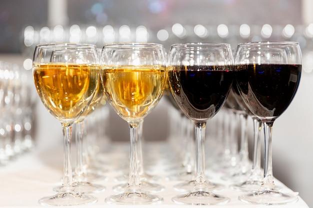 Filas de vasos con vino tinto y blanco en la mesa de buffet festivo. salida de registro de eventos.