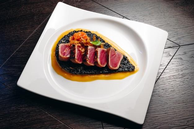 Filete de atún tataki con risotto negro y salsa de mango