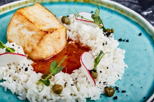 Filete de bacalao con arroz y salsa en un plato azul