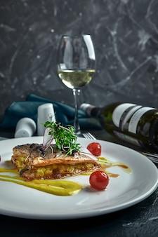 Filete blanco de pescado a la plancha sobre almohada de verduras y salsa amarilla, con tomates y hierbas frescas. pesque en la placa blanca con el vino blanco en la pared hermosa oscura. de cerca. espacio