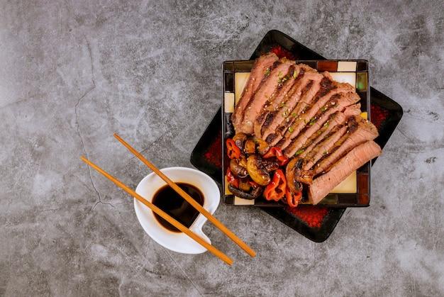 Filete de carne asada en rodajas al estilo chino, champiñones, semillas de sésamo, salsa de soja con palillos