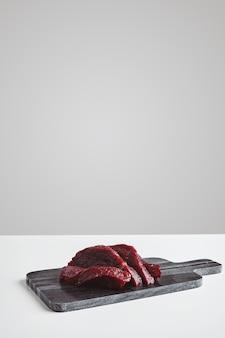 Filete de carne de ballena cruda de primera calidad en rodajas en una tabla de cortar de piedra de mármol aislada en una mesa blanca