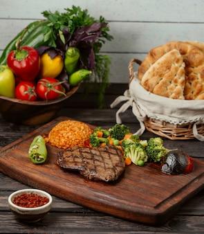 Filete de carne en un baord de madera con hierbas y arroz.