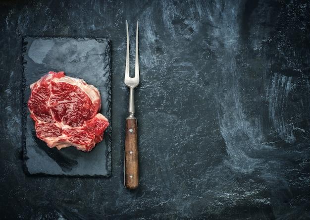 Filete de carne cruda en la placa de piedra sobre la mesa negra.