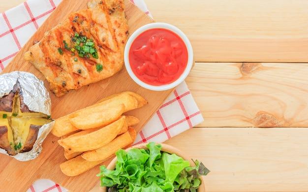 Filete de carne a la parrilla con salsa de tomate y ensalada de verduras sobre fondo de madera