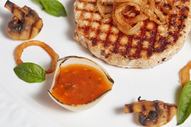 Filete de carne a la parrilla con verduras y salsas en un plato