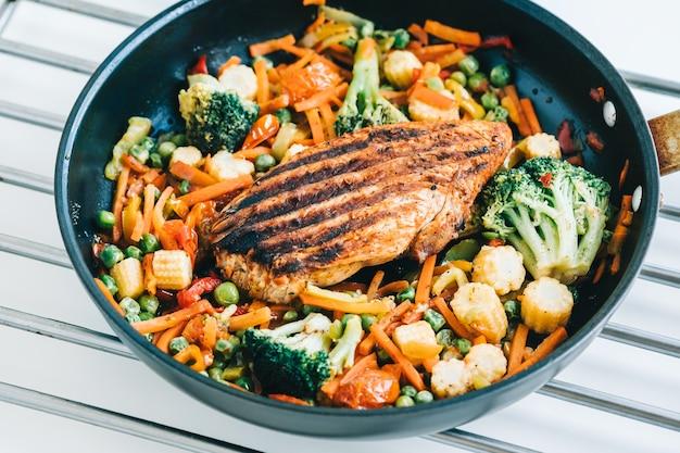 Filete de carne de pavo a la plancha y verduras fritas se mezclan en una sartén negra sobre la mesa blanca.