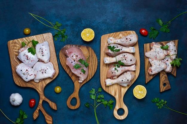 Filete de carne de pollo crudo, muslo, alas y patas con hierbas, especias, limón y ajo sobre fondo azul oscuro. vista superior
