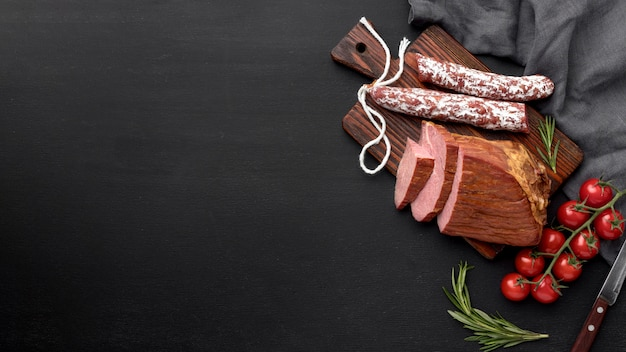 Filete de carne y salami sobre tabla de madera con espacio de copia
