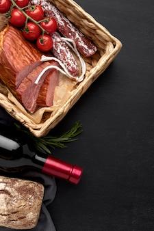 Filete de carne y salami sobre tabla de madera y tomates