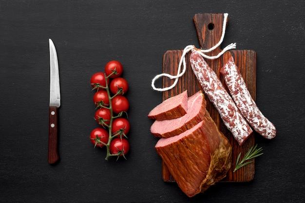 Filete de carne y salami sobre tabla de madera y verduras