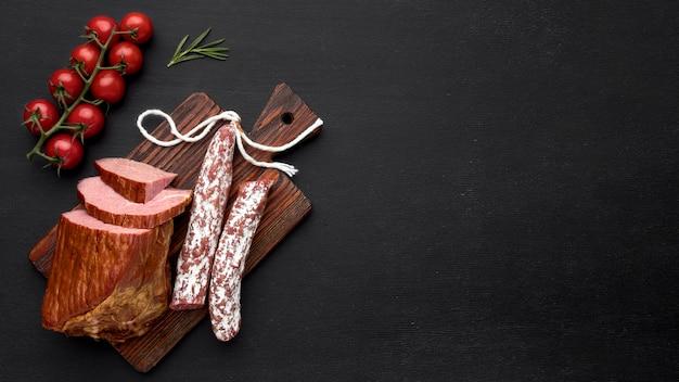 Filete de carne y salami con tomate y espacio de copia