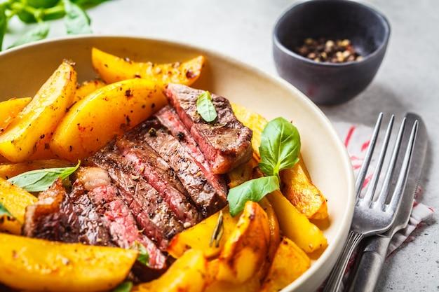 Filete de carne de vaca asado a la parrilla con las patatas y albahaca en una placa blanca en el fondo blanco.
