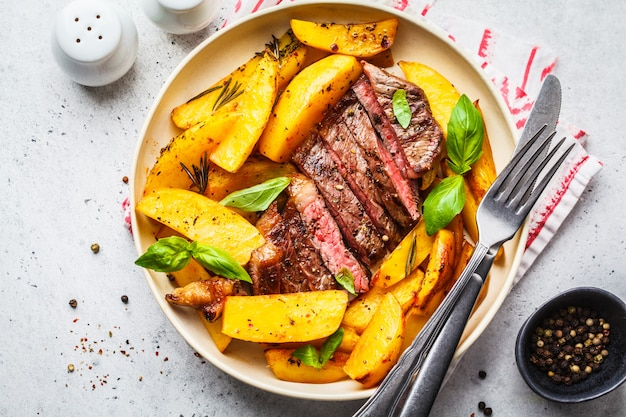 Filete de carne de vaca asado a la parrilla con las patatas y albahaca en una placa blanca, visión superior.