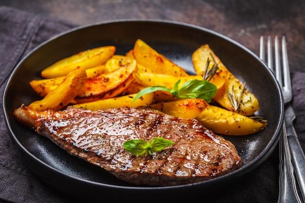 Filete de carne de vaca asado a la parrilla con las patatas y albahaca en una placa negra en fondo oscuro.