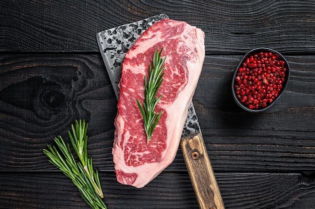 Filete de carne de vacuno crudo fresco de nueva york en una cuchilla de carnicero. fondo de madera negra. vista superior.