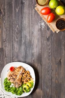 Filete de cerdo cocina casera con especias hojas de lechuga en tabla de cortar de madera y un plato