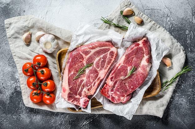 Filete de cerdo fresco. carne de mármol sobre papel pergamino. pared gris. vista superior. espacio para texto