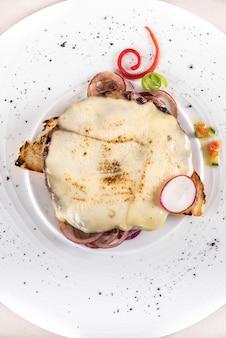 Filete de cerdo con queso, colocado sobre una tostada y cebolla roja, decorado con hojas verdes y rojas