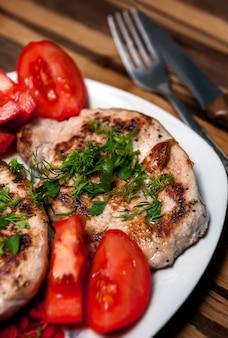 Filete de cerdo con tomate y hierbas frescas.