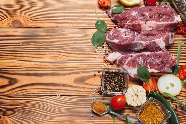 Filete de chuleta de cerdo cruda preparar en cocina con verduras y especias