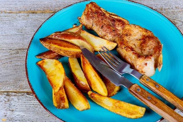 Filete de chuletón a la plancha, medio raro, cortado en rodajas y papas fritas en primer plano