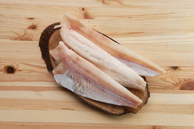 Filete congelado de panga en mesa de madera