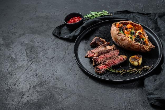 Filete de costilla adornado con camote al horno. carne asada. carne de granja ecológica.