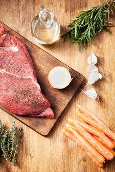Filete crudo con ajo y zanahorias sobre fondo de madera. preparación de comida. ingredientes naturales.